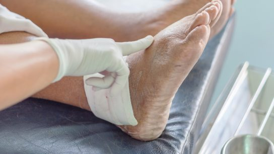 Gloved clinician touching foot