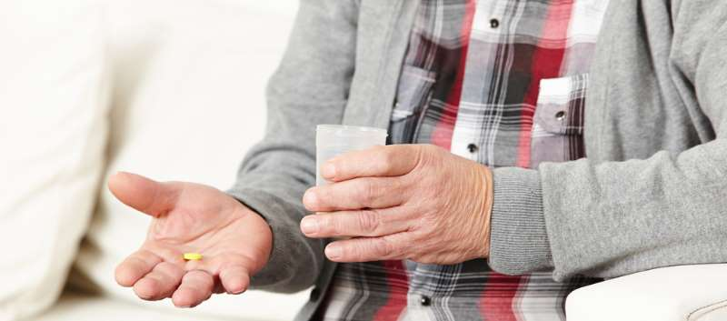 elderly man with pill and water