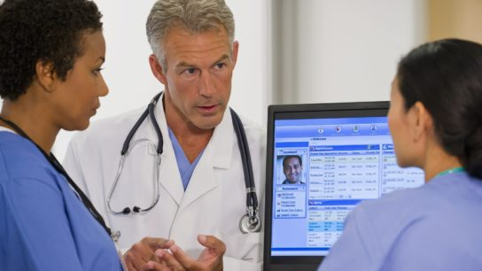 Clinicians talking with an electronic health record showing on the screen