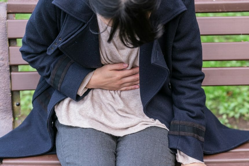 Woman with stomach pain sitting on bench