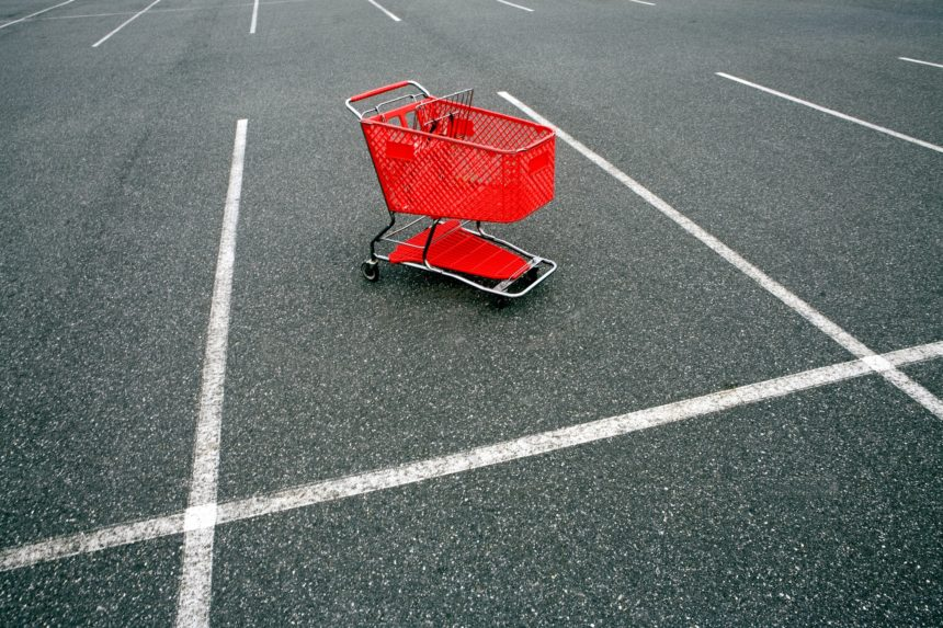 Empty red shopping trolley in car park space