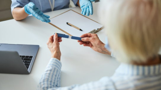 Senior patient talks about autoinjector with her doctor.